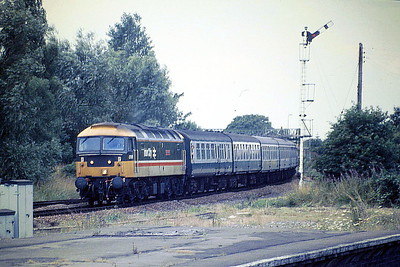 47618 FAIR ROSAMUND runs into March Station with an SSO Yarmouth Special, 07/87. 47618 was built by Crewe Works in 1964 as D1609 and was renumbered to 47030 in December 1973. It was ETHed and renumbered to 47618 in August 1984. In August 1989 it was converted into long range 47836, reverting to 47618 in April 1993 and was then fitted for multiple working and renumbered 47780 in January 1994. It was withdrawn in May 2003 and scrapped in August 2007.