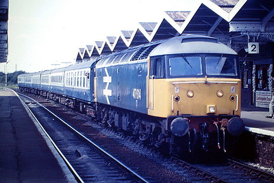 47614 makes its March Station stop on the Blackpool - Cambridge, 21/08/85.47614 was built by Brush Falcon Works in 1964 as D1733 and was renumbered to 47141 in January 1974. This was the original XP64 loco. It was ETHed and renumbered to 47614 in July 1984 In February 1990, it was converted to twin tank 47853 in 2001, Virgin Trains reliveried in something like XP64 livery. It was withdrawn in November 2002 and sold to Riviera Trains, who sold it in October 2006 to DRS who in turn sold it to Locomotive Services Ltd. in August 2018, where it now runs as 47614 again.