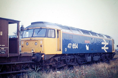 47654 FINSBURY PARK is weekending at March Depot en route to Scotland in tow, 09/87. Strange name for a Scottish loco! 47654 was built by Crewe Works in 1964 as D1640 and was renumbered to 47056 in February 1974. It was ETHed and renumbered to 47654 in May 1986. In July 1989 it was fitted for multiple working as 47783. It was withdrawn in June 2002 and scrapped in November 2007.