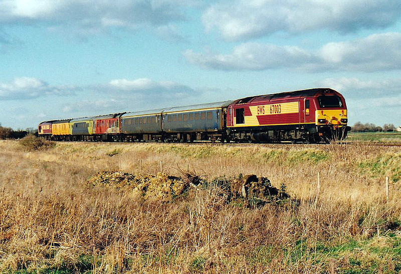 67003, top'n'tailed by 67012, heads an eastbound Serco test train past Welney Road LC, 08/02/06.