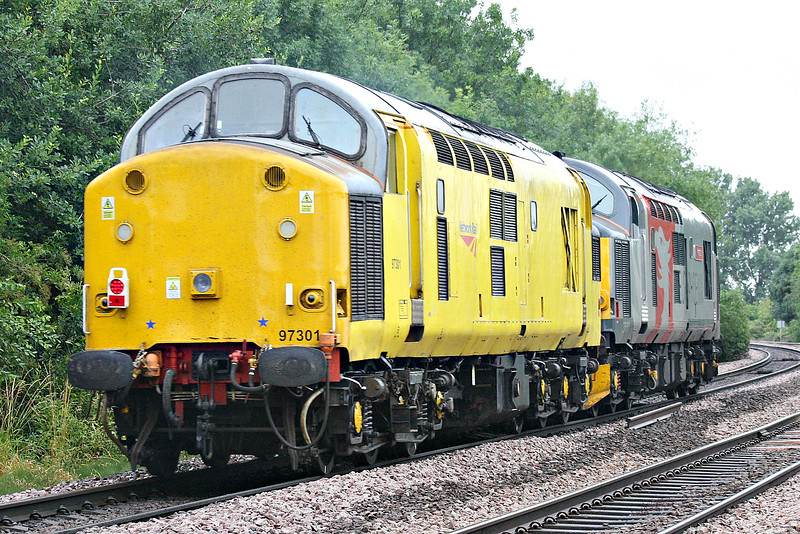 97301, formerly 37100, owned by Network Rail, passes Badgeney Road AHB in tow of 37611 PEGASUS, owned and operated by Europhoenix Ltd., on a Cambridge - Derby RTC train, 28/06/17. 97301 had failed at Cambridge on test train the pervious week.