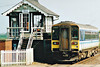 Class 153 309 passes the little signalbox at Manea on a Peterborough - Ipswich service, 19/05/98.