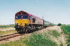 THE FENMAN - 66250 heads the train back just past Redmoor Lane towards March along the Wisbech Branch, 12/05/01.<br /> The 'Fenman' Rail Tour ran with 66076/66250 providing power as follows:<br /> 66250 Kings Cross - (via ECML) - Peterborough <br /> 66076 Peterborough - March West Jn - Wisbech  <br /> 66250 Wisbech - March - Ely (via the West Curve)<br /> 66250 Ely - Kings Lynn Yard <br /> 66076 Kings Lynn Yard - Middleton Towers <br /> 66250 Middleton Towers - Kings Lynn Yard <br /> 66076 Kings Lynn Yard - Ely - Cambridge - Hitchin - (via ECML) - Kings Cross.<br /> The train was booked to use the newly-laid East Curve at March but it was not officially opened yet and none of the signals were working - mass panic ensued and the train was only passed to use it at the eleventh hour.<br /> This was the last train ever to run over the entirety of the Wisbech Branch as then existed.