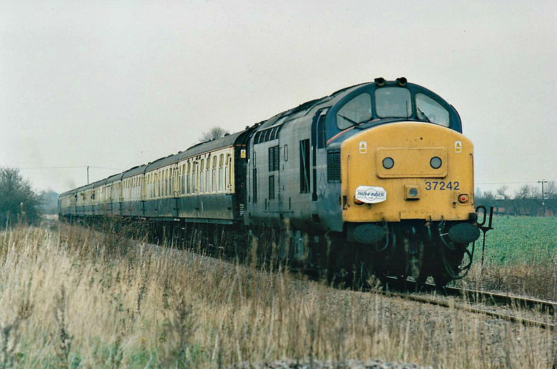 THE CROMPTON PEDIGREE - 37242 brings up the rear of the 'Crompton Pedigree' Railtour heading north on Wisbech Branch from the Black Bridge, 21/11/98. This loco was withdrawn in 12/99 and scrapped.<br /> 33103 Crewe - Stafford - Wolverhampton - Birmingham New Street - Proof House Jn - Landor Street Jn - Water Orton - Nuneaton - Hinckley - Wigston North Jn - Leicester - Stamford - Helpston Jn - New England Yard - Peterborough - March West Jn - Whitemoor Jn - Wisbech (Weasenham Lane LC) <br /> 37242 Wisbech - Whitemoor Jn - March West Jn<br /> 33103 March West Jn - Whitemoor Jn <br /> 37242 Whitemoor Jn - March East Jn - Ely West Jn - Ely North Jn - Ely <br /> 33103 Ely - Ely North Jn - Downham Market - Kings Lynn Yard <br /> 37242 Kings Lynn Yard - Middleton Towers <br /> 33103 Middleton Towers - Kings Lynn Yard <br /> 37242 Kings Lynn Yard - Downham Market - Ely North Jn - Ely West Jn - March - Whittlesea - Peterborough<br /> 33103 Peterborough - Helpston Jn - (reverse of outward route) - Crewe.<br /> Due to the signalmen giving wrongly directed, the train sent around the West Curve at Whitemoor Junction and had to stop and reverse, then taking the East Curve.