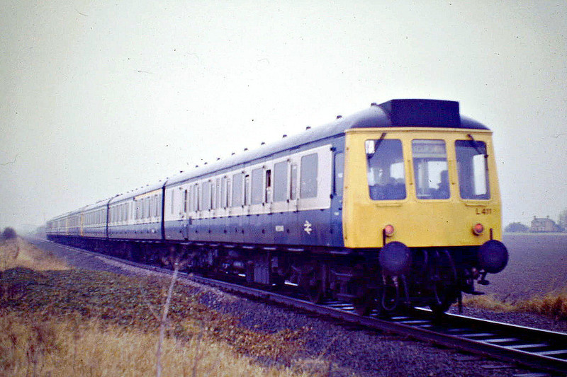 THE ANGLIA VIBRATOR - Class 117 3-car DMU L411 brings up the rear of the 'Anglia Vibrator' Railtour as it passes the site of Coldham Station on the Wisbech Branch, 23/11/85. The tour was aptly named as these WR Paddington suburban sets were not sumptuously appointed.<br /> Leg 1 - London  Kings Cross - Potters Bar - Hitchin - Cambridge - Ely - March - March West Jn - Wisbech Goods<br /> Leg 2 - Wisbech Goods - Ely West Jn - Ely North Jn - Wymondham<br /> Leg 3 - Wymondham - North Elmham <br /> Leg 4 - North Elmham - Wymondham<br /> Leg 5 - Wymondham - Brandon - Ely - Cambridge - Hitchin - Potters Bar -  London Kings Cross.<br /> You can easily see what sort of a day it was!
