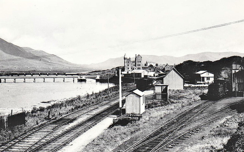 CAHIRCIVEEN STATION - looking north, on the Farranfore - Valentia Harbour branch. The station was opened in September 1893 and closed in February 1960. The steel viaduct on the left is still in situ. Note the engine shunting on the right whilst the stock of the mixed train sits in the platform - seen here in September 1938.