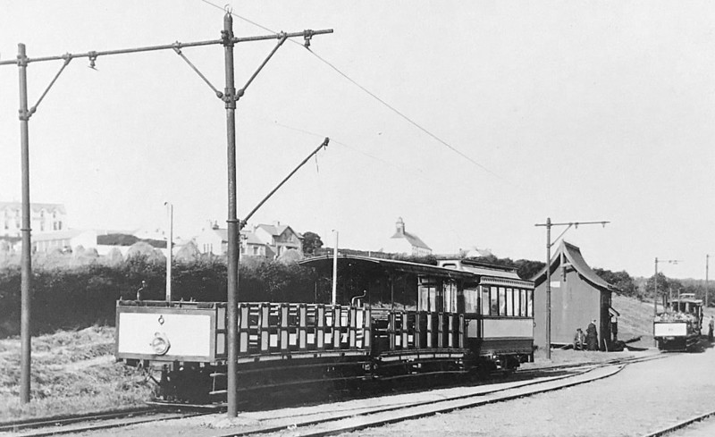 A 'toast-rack' open tram with 2 trailers sits in the passing loop at Bushmills as another approaches - note tiny station building - seen here in 08/30.