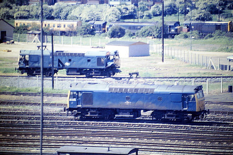 25205 had just come off a train in the Down Yard at Toton and en route for Depot, passing the much mangled 25151 in the Training Compound. 05/85. The loco was withdrawn in May 1986.