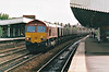 66002 heads west through Leamington Spa on a rake of MGR empties, 04/06/99.