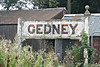 GEDNEY - Opened in July 1862 on the Sutton Bridge to Spalding line, first stop west of Long Sutton, there are Gedney's scattered about all over this part of the Fens. The station had two platforms to provide a passing place and a small goods yard, being almost identical with Fleet, the adjacent station. One of the old station platform signs still survives, albeit somewhat knocked about and removed from it's original home. These were made of concrete, a material of which Mr. Marriott, ever keen to save a few pence, was an early champion. They were made at Melton Constable Works, where they also made most of the other paraphernalia necessary to run a railway, such as fences, benches, gates. Seen here on 23.08/17.