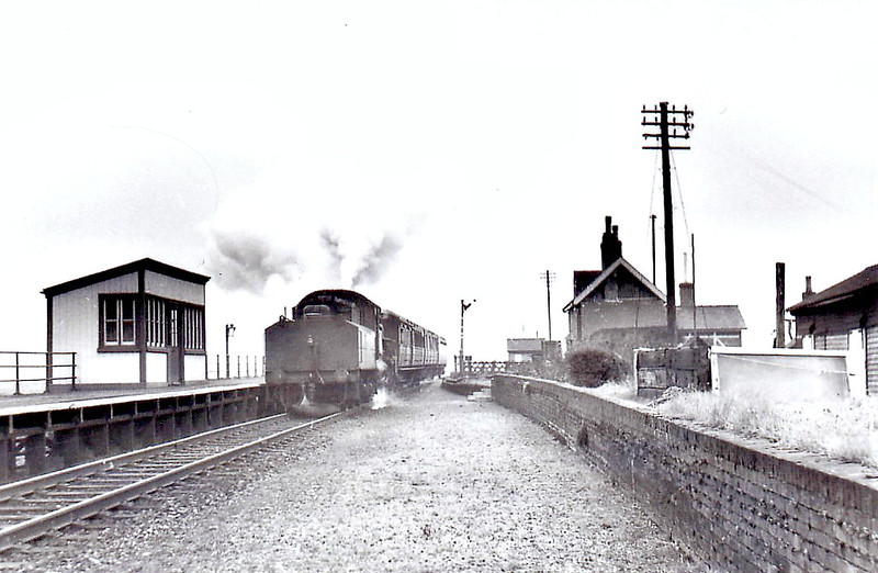 NORTH DROVE - Opened in August 1866 by the Spalding & Bourne Railway, North Drove Station really was in the middle of nowhere, the nearest, very small village being Pode Hole, about half a mile away. The station closed to all traffic in September 1958 and this shot a an Ivatt Class 4MT 2-6-0 on a Bourne train is probably from about that time. Although provision has been made for a passing loop, none was ever built and the small wooden shelter was the only passenger accommodation provided.