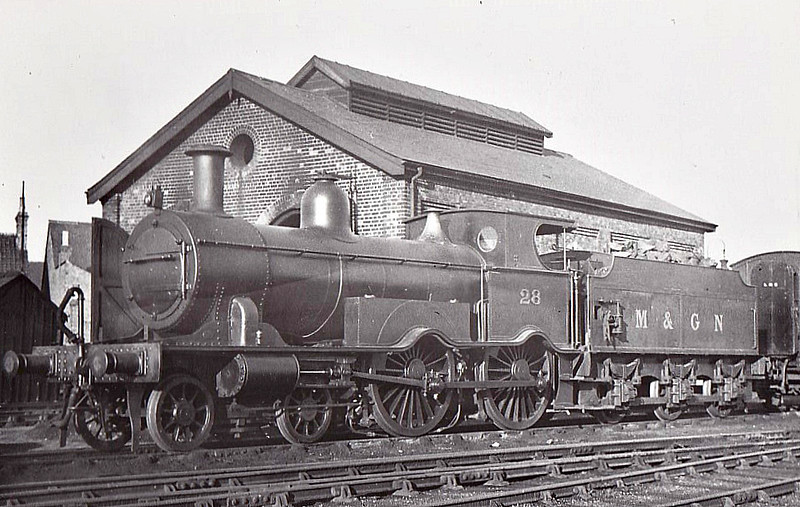 M&GN - 28 - Eastern & Midland Railway M&GN Class A 4-4-0 - built 1883 by Beyer Peacock Ltd., Works No.2341, as E&MR No.28 - LNER No.028 not applied - 02/38 withdrawn - seen here at Spalding  after rebuild with extended smokebox, extended cab roof, round cab windows, sandboxes to the rear of the splashers for tender-first running and removal of numberplates.