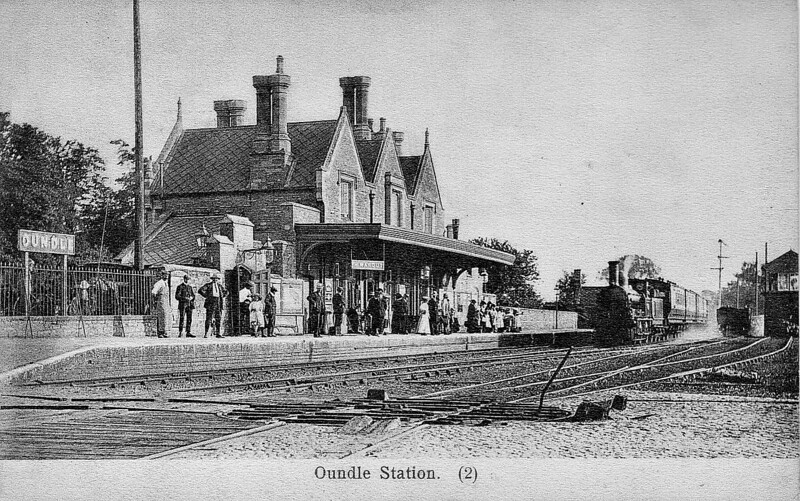 OUNDLE STATION - opened in 1845 on the Peterborough - Northampton line, with a substantial stone station building and staggered platforms. The station closed to regular traffic in 1964, remaining open for public school special trains until 1972. The building still exists as a residence. Strangely, this Peterborough train, hauled by an LNWR 'Coal Engine' 0-6-0, is arriving at what would usually be the westbound platform. Perhaps this platform was more convenient than the other if there were no conflicting movements.
