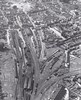 KINGS LYNN - An aerial view from 1950. The station itself would not seem so radically different today but everything else had changed enormously. In the bottom right corner we have the harbour lines serving the docks, still in place but unused. Most of the extensive goods yard is now covered in superstores and the locoshed, no doubt crammed with 'Clauds', J17's, B17's and J69 tanks, is but a distant memory. Kings Lynn, although a terminus, was also a major junction with lines radiating out to Hunstanton, Norwich, Wisbech and Liverpool Street plus the shuttles to the M&GN at South Lynn. Only the mainline to London now remains.