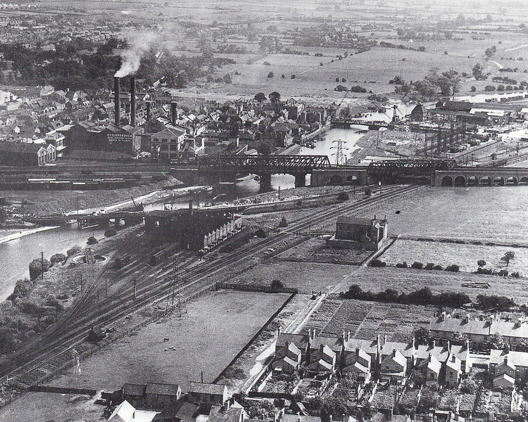 PETERBOROUGH - A view looking east in July 1932 showing Peterborough's major railway junction. The Great Northern mainline runs right to left to right with LNWR lines from Northampton and Rugby running under the GNR and into Peterborough East, just out of shot to the right.  The LNWR locoshed, apparently in use as a carriage shed, stands in the foreground, with Nene carriage sidings and the line coming in from Leicester behind it. The two chimneys belong to the old power station. In the distance, cranes be seen on the town river bridge. Works had just started to replace this bridge and carry south as far the football ground to create the current bridge, completed in 1934. Note the total lack of development east of the bridge. As a youth, my favourite trainspotting location was 'East crosses North', about where the two carriages stand just beyond the GNR mainline. Three routes converged there and, even in the mid '60's, steam was still abundant.