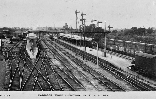 PADDOCK WOOD, Kent - Opened in August 1842 by the South Eastern Railway on the line from Tonbridge to Marden. There were two main platform faces, with through lines between them and a bay platform on each side. That on the left served Medway Valley services to Maidstone whilst that on the right was used by Hawkshurst branch trains. The row of coaches stabled on the right look fairly primitive in this early 20th Century view. The station handles 1.3 million passengers per year to and from Charing Cross.