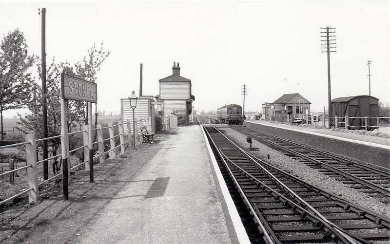 STONEA - Between March and Manea, it served just a cluster of farms, a few cottages and a pub. Opened in 1847, it closed in 1966 and is seen here in about 1960 with a Derby Lightweight DMU approaching from March. Note the gas lamp. Interestingly, Stonea boasts one of the few sets of manually operated level crossing gates still in action.