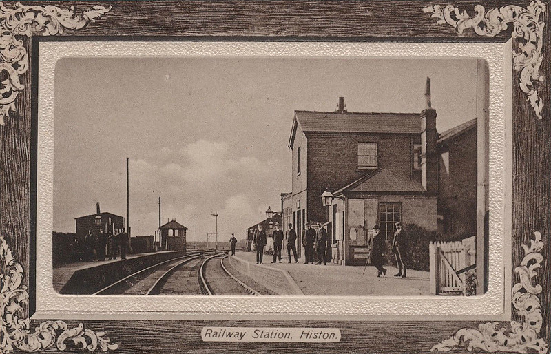 HISTON - Opened by the Great Eastern Railway on its Cambridge - St Ives line in August 1847, the station closed in August 1970, although the line remained in use for sand traffic until 1992, only to be replaced by the Cambridge - St Ives (Mis)guided Busway. Not visible in this picture is large goods yard that the served the adjacent Chivers jam factory, perhaps accounting for what seems to be a large staff for such a relatively minor station. Seen here in about 1910.