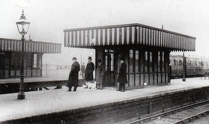 SAXBY - On the mainline between Melton Mowbray and Oakham, the station was opened in 1849 and then considerably enlarged in 1894 when the Midland & Great Northen Joint Railway mainline made its junction here. This view shows King Edward VII (grey overcoat with dog) waiting for a train with his retainers, presumably en route to Sandringham. Note all of the heads hanging out the carriages off to the right.