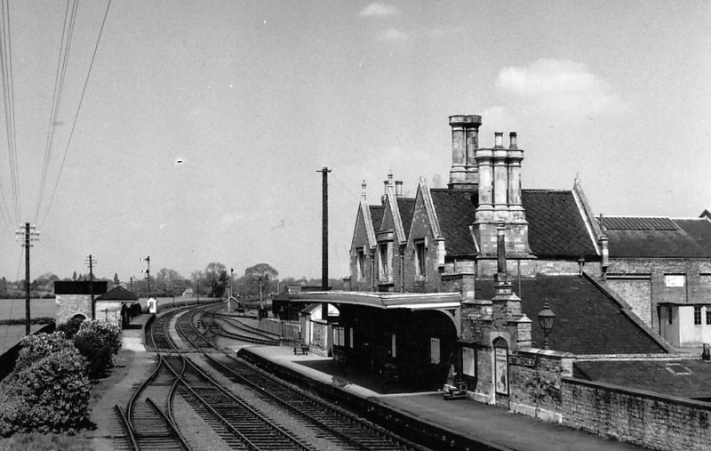 OUNDLE STATION - opened in 1845 on the Peterborough - Northampton line, with a substantial stone station building and staggered platforms. The station closed to regular traffic in 1964, remaining open for public school special trains until 1972. The building still exists as a residence. The track bed behind the photographer is now a bypass. Seen here in the 1950's I think.
