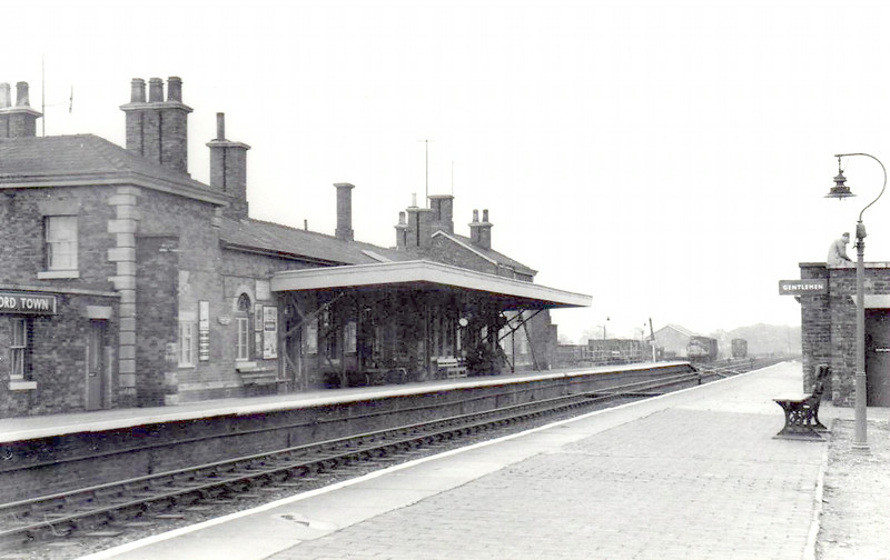 ALFORD TOWN - Opened in 1848 on the line from Louth to Boston, renamed  Alford Town in 1923 to distinguish it from at least 2 other Alford's. Unusually, the station closed to freight traffic first, in 1966, and to passengers in 1970. I'm not sure what the bloke on the roof of the Gents is up to but I'm sure you can be arrested for it!