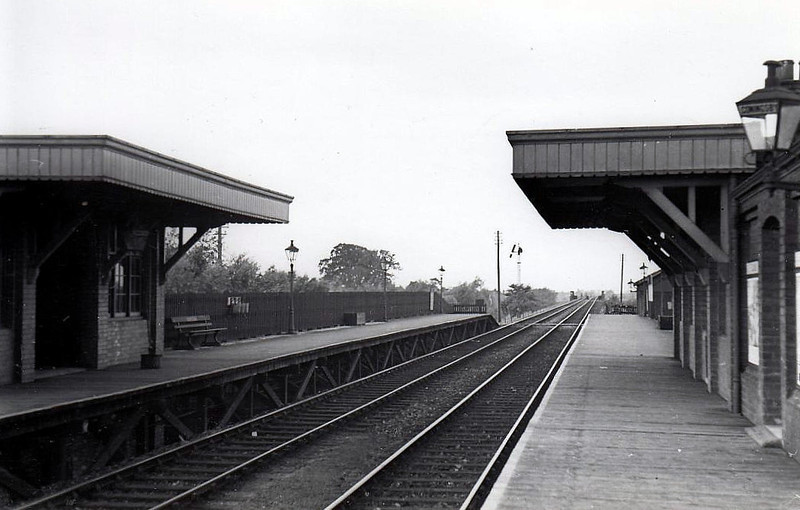CONINGSBY - First station on the Woodhall Junction - Little Steeping cut-off line that allowed Lincoln trains direct access to Skegness without the need to run round at Boston. Built of timber on an embankment, closed to all traffic in October 1970. Note gas lamps and somersault signal in off position.