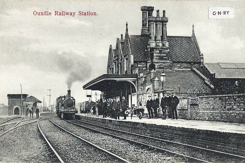 OUNDLE STATION - opened in 1845 on the Peterborough - Northampton line, with a substantial stone station building and staggered platforms. The station closed to regular traffic in 1964, remaining open for public school special trains until 1972. The building still exists as a residence. I suspect that this view is in about 1900 with a Northampton train entering the station and all staff assembled - there are a lot of them, including the shunting horse on the left!