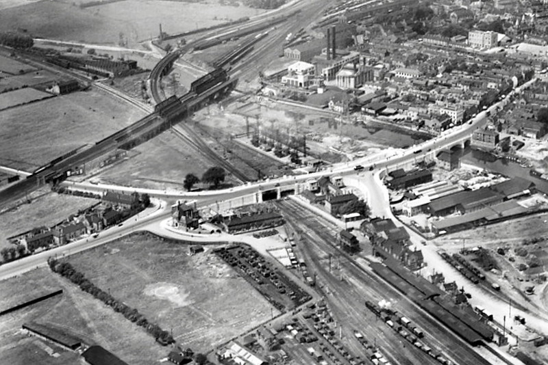 PETERBOROUGH EAST - In the bottom right hand corner of this picture is Peterborough East, giving a good idea of it's curiously camped layout. The LNWR locoshed is in the top left corner. The town bridges look new, having been completed in 1934, quite a considerable feat of engineering for that period. Note the football ground in the bottom left corner. Peterborough United turned professional in 1934 so no doubt London Road changed quickly thereafter.  The two tall chimneys belong to the coal-fired power station, demolished in the '80's