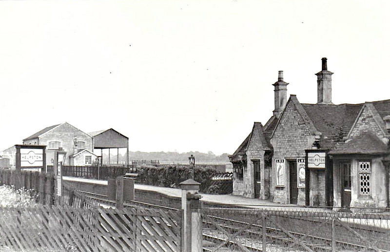 HELPSTON - A few miles north of Peterborough on the Syston and Peterborough Railway, opened in October 1846 and closed in June 1966. Many of the stations on this line were built of local stone in a cottage style. The picture is taken from the island formed by the separation of this line and GNR mainline. The goods shed is still in use as a private dwelling.