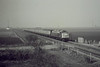 RAIL TOUR - 'WHISTLER FINALE' - organised by TP Railtours and run on March 9th, 1985. 40122, ex D200, approaches the A141 Bridge on this tour to mark the end of Class 40 in regular traffic. The tour ran as follows:-<br /> <br /> D200 - York - Church Fenton - Micklefield - Cross Gates - Leeds - Gelderd Road Jn - Wakefield Westgate - South Kirkby Jn - Doncaster - (via ECML) - Grantham - Peterborough - Whittlesea - March - Ely - Chippenham Jn - Bury St Edmunds - Ipswich - Harwich Parkstone Quay<br /> - Manningtree - Colchester - Chelmsford - Stratford - approx 1/4 mile short of London Liverpool Street (to avoid run round in station and allow D200 to go for fuel).<br /> 31225 - approx 1/4 mile short of London Liverpool Street - London Liverpool Street<br /> D200 - London Liverpool Street - Bethnal Green - Hackney Downs - Clapton Jn - Cheshunt - Broxbourne - Cambridge - Ely - (reverse of outward route) - Grantham (missed Grantham stop and had to reverse about 1 mile) - (reverse of outward route) - York.