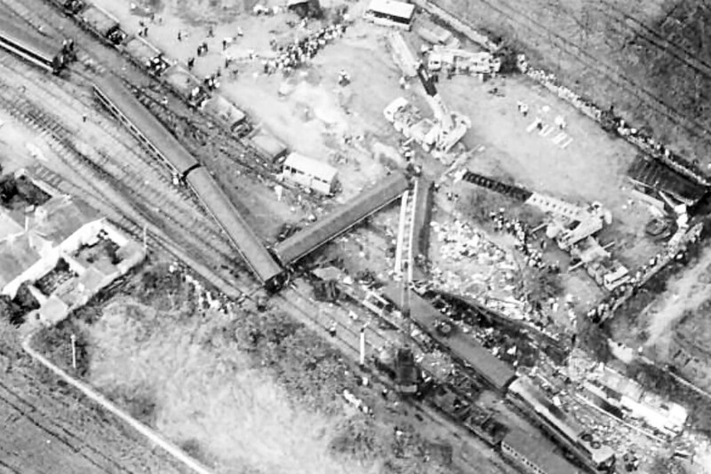 BUTTEVANT - On August 1st, 1980 at 1245, the 1000 Dublin (Heuston) to Cork (Kent) express train entered Buttevant station carrying some 230 bank holiday passengers. The train was diverted off the main line across a temporary set of points into a siding. The locomotive remained upright but carriages immediately behind the engine and generator van jack-knifed and were thrown across four sets of rail lines. Two coaches and the dining car were totally demolished by the impact. It resulted in the deaths of 18 people and over 70 people being injured.<br /> The accident happened because a set of manual facing points were set to direct the train into the siding. These points were installed about four months previously and had not been connected to the signal cabin. The permanent way maintenance staff were expecting a stationary locomotive at the Up platform to move into the siding and had set the points for the diversion to the siding, without obtaining permission from the signalman. Upon seeing that this had been done, the signalman at Buttevant manually set the signals to the Danger aspect and informed the pointsman to reset the points. The train was travelling too fast to stop in time. The derailment occurred at around 60 mph.<br /> The train consisted of 071 Class locomotive number 075, a generator van and 11 coaches. Six of the coaches consisted of wooden bodies on steel underframes. Four of these were either destroyed or badly damaged in the impact, the two which survived being at the rear of the train. The remainder of the coaches were light-alloy Cravens stock, most of which survived the crash. The generator van, a modified BR Mark 1, was severely damaged. All of the vehicles were coupled using screw shackle couplings. This event, and the subsequent Cherryville junction accident, which killed a further seven people, accounted for 70% of all Irish rail deaths over a 28-year period. CIÉ and the Government came under severe public pressure to improve safety and to mode