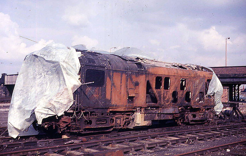CHESTER - On May 8th 1972, Class 24 5028 ran away on the approach to Chester station and caused considerable damage to itself, several diesel multiple units and much of the station fabric around Platforms 10 & 11. 5028 had been in charge of the 8D66 1931 Ellesmere Port to Mold Junction freight consisting of thirty eight vehicles including several tank wagons loaded with petroleum products. The train had been made up at Ellesmere Port East Yard with a total weight of 980 tons. Beyond the reversal at Helsby, the five vacuum braked tankers were marshalled directly behind the engine to provide extra brake force but the vacuum hoses were not connected between the locomotive and the tank wagons. For reasons undetermined the train set off without a brake test being carried out. About a mile and a half from Chester station the grade on the line from Mickle Trafford falls at 1 in 100 for about a mile and it was on this grade that control of the train was lost, with the driver sounding a series of short blasts on the locomotive horn, indicating the train was running away. Unfortunately the means of putting the runaway train on to one of the through lines was prevented by the movement of a diesel multiple unit betweens Platform's 11 & 13. With the freight train routed into the bay Platform 11 events happened swiftly, the driver and a second railman jumped from the locomotive as it entered the platform at about 20mph. Standing at the end of the platform were empty diesel multiple units 56229 & 50946. The trailer composite (56229) lost both bogies with major damage to the underfloor equipment occurring when it was pushed over the buffer stops onto the platform and coming to rest embedded in the wall of the refreshment room. The motor brake second (50946) was completely demolished as 5028 rode up over it. The brake van next to the locomotive was severely damaged, four of the tank wagons sustained damage from the collision, particularly to the running gear. Despite the severity of the collision none of the loaded tanks were punctured. Shortly after the collision fire broke out under the remains of the diesel multiple unit crushed by 5028. A locomotive waiting at the east end of the station was used to haul back thirty five wagons of the freight train, the split being made between the third & fourth tank wagon. Passengers from the diesel multiple unit standing at Platform 10 were quickly evacuated to the running lines in the centre of the station. A postal worker was trapped on the platform between the diesel multiple unit and an overturned BRUTE trolley loaded with mail bags. Rescue attempts were unsuccesful until the front two coaches of the diesel multiple unit were separated from the other three, creating room to free the postal worker. Although the three Esso tanks remained unpunctured the fire was intense enough to heat the contents of the second tank, pressurising the liquid which then ignited after being released through the pressure relief valve. The first tank, lying on its side lost some of its contents through the syphon pipe, and was ignited from the original fire source. The third tank suffered no spillage or leakage due to the efforts of the fire service, using foam and water to contain the fire. The fire was contained just prior to midnight and finally extinguished about thirty minutes later, although the tanks remained in a dangerous condition for a further nine hours. For 5028 the examination next morning revealed it to be a total loss. The leading cab was severely crushed, the trailing cab had lost most of its aluminium structure in the fire, which also destroyed (melted?) the radiators and buckled the engineroom floor. The brake gear had been badly damaged in the collision though it did not reveal signs of heavy braking.
