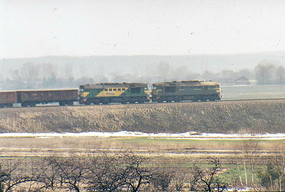 A pair of ST44's throb westwards on the considerable climb from Kozlow to cross the mainline on a loaded ore train for Slawkow, Winter 2007. The leading loco is in the old LHS livery whilst the second is in the newer livery.