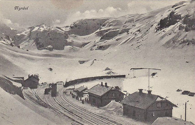 NORWAY - the islolated station at Myrdal, which has no road connection to the outside world. It is situated on the mainline north from Bergen and is at the head of the Flam Line to Sognefjord. There is a hotel and few cottages but no village. Seen here in about 1910, a failry substantial steam train is seen arriving in the depths of winter. Note the small locomotive depot on the left.