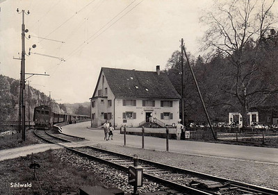 SWITZERLAND - SBB - an old Box Cab type loco passes the Gasthof Forsthaus as it approaches Sihlwald Station.