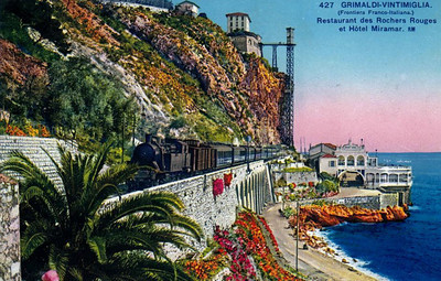 ITALY - GRIMALDI VINTIMIGLIA - a passenger train passes along the seacoast on the French/Italian border. The restaurant of the Hotel Mirmaar is on the beach whilst the hotel is on the clifftop.