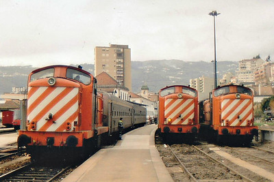 PORTUGAL - CP - 1414 - 67 Class 1400 Bo-Bo engines built in 1967 for light passenger/freight duties - about 20 still in traffic - is about to depart on a passenger trsin whilst sisters stand in the platform and the engine sidings.