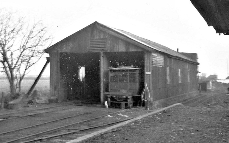 SELSEY TRAMWAY - The locoshed at Chichester with one of the railcars poking out. In 1924, Stephens was seeking means of reducing operating expenses and acquired two railcars built on Ford Model T chassis, with bodies by Edmunds of Thetford. They operated together, back-to-back with a truck for luggage and parcels between them; they had rails on the roof to contain additional parcels stowed there. Two more railcars were acquired from the Shefflex Motor Company of Tinsley in 1928; they too operated as a unit with a truck between. The railcars were provided with a crude timber buffer beam in front of the radiator, as protection. <br /> The Hundred of Manhood and Selsey Tramway, to give its full title, ran from Chichester to Selsey, a distance of 7.25 miles, and opened to Selsey Town in August 1897. In 1898, the line was extended to Selsey Beach, this exrension closing in 1908. The line prospered until the early 1920's but thereafter traffic dropped off alarmingly and the line closed in 1935.