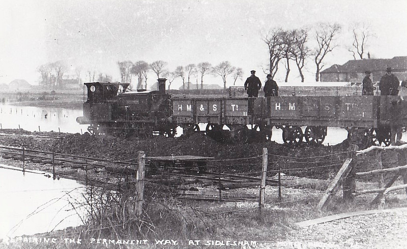 SELSEY TRAMWAY - SIDLESHAM - 0-6-0ST built by Manning Wardle & Co. in 1861 - bought from industrial contractors - seen here on a works train at Sidlesham after the disastrous floods of December 15th, 1910, which completely inundated the line.<br /> The Hundred of Manhood and Selsey Tramway, to give its full title, ran from Chichester to Selsey, a distance of 7.25 miles, and opened to Selsey Town in August 1897. In 1898, the line was extended to Selsey Beach, this extension closing in 1908. The line prospered until the early 1920's but thereafter traffic dropped off alarmingly and the line closed in 1935.