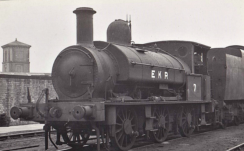 EAST KENT LIGHT RAILWAY - No.7 - Beattie LSWR 0-6-0ST - built 1882 by Beyer Peacock & Co. as LSWR No.127 - 01/26 sold to EKR - 1936 new smokebox fitted in place of original sloping front type - 09/44 withdrawn - 03/46 scrapped at Ashford, where seen.<br /> The East Kent Light Railway was part of the Colonel Stephens group of cheaply built rural light railways in England. Holman Fred Stephens was engineer from its inception, subsequently becoming director and manager. The line ran from Shepherdswell to Wingham (Canterbury Road) Station with a branch from Eastry through Poison Cross to Richborough Port. Built primarily to serve colliery traffic, the line was built with many spurs and branches to serve the mostly unsuccessful mines of the Kent coalfield, with cancelled plans to construct several others. The success of Tilmanstone colliery allowed the main line of the railway to continue operation until 1986, when the remainder of the line became a heritage railway.