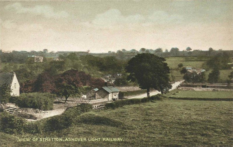 ASHOVER LIGHT RAILWAY - An official Ashover Light Railway postcard showing a view of Stretton village, what there is of it. The railway can be seen in the centre background crossing the road.<br /> The Ashover Light Railway was a 597 mm narrow gauge railway in Derbyshire that connected Clay Cross and Ashover. It was built by the Clay Cross Company to transport minerals such as limestone, fluorite, barytes and gritstone to its works at Clay Cross. The line was 7.25 miles long and opened to goods traffic in 1924 and to passenger traffic in March 1925. The line was built using surplus equipment from the War Department Light Railways. Although the line was built principally to carry mineral traffic, its passenger service proved successful during the mid-1920s, but competition from buses saw numbers decline and passenger services were withdrawn in 1936.  The mineral traffic continued but the railway declined through the 1940's. In 1949 the railway's last remaining contract with Butts quarry was terminated and the quarry closed in 1950. The railway closed on 31 March 1950.