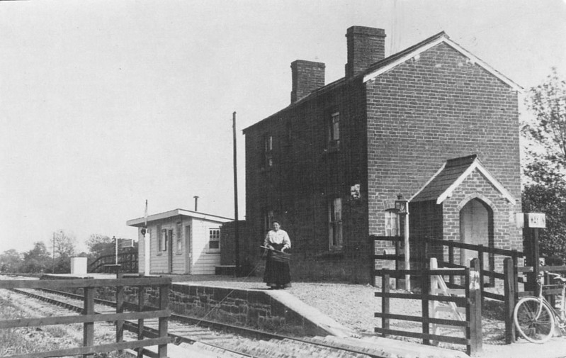 SHROPSHIRE & MONTGOMERYSHIRE LIGHT RAILWAY - MAESBROOK STATION - This was the last station before Llanymynech and, as can be plainly seen, facilities were not lavish but no doubt sufficient to handle the traffic generated. This lady is probably the entire staff. It closed in 1933 along with the rest of the railway.<br /> The Shropshire & Montgomeryshire Light Railway was a railway running from Shrewsbury to Llanymynech, Wales, opened in 1911 with a branch to Criggion. It was part of Colonel Stephens' railway empire. The line was taken over by the War Department in 1941, and extensively reconstructed to serve Central Ammunition Depot Nesscliffe. It was finally closed in 1960.