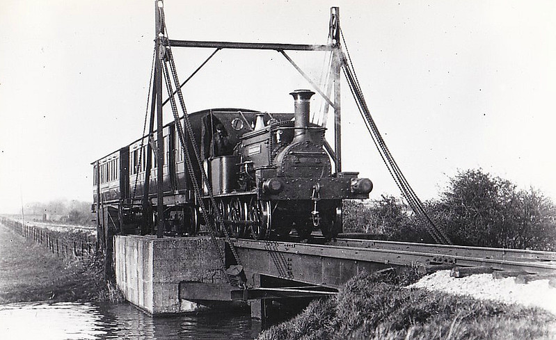 SELSEY TRAMWAY - SIDLESHAM - 0-6-0ST built by Manning Wardle & Co. in 1861 - bought from industrial contractors - seen here crossing the lifting bridge near Hunston.<br /> The Hundred of Manhood and Selsey Tramway, to give its full title, ran from Chichester to Selsey, a distance of 7.25 miles, and opened to Selsey Town in August 1897. In 1898, the line was extended to Selsey Beach, this extension closing in 1908. The line prospered until the early 1920's but thereafter traffic dropped off alarmingly and the line closed in 1935.
