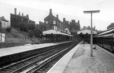 BIRKENHEAD CENTRAL - Opened in 1886, it lies on the Chester and Ellesmere Port branches of the Wirral Line, now part of the Merseyrail network. It was the headquarters of the Mersey Railway and the location of the motive power depot. Seen here after electrification with an EMU in the bay platform, it still handles about 1 million passengers per year.
