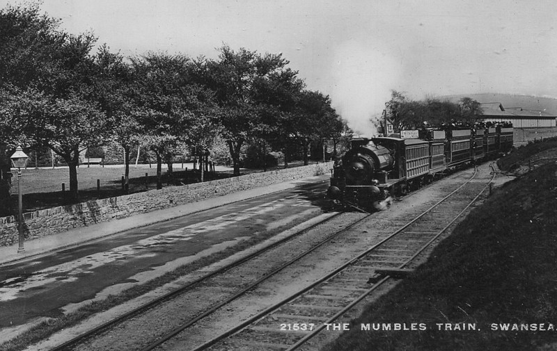 SWANSEA AND MUMBLES TRAMWAY - A train hauled by a Saddle Tank heads for Mumbles. I am unable to find any information on the locomotives except that three were called CRUMLYN, SWANSEA and HAMPSHIRE. The passing loop does not seem to be operative either.<br /> The Swansea and Mumbles Railway was the world's first passenger railway service. Originally built under an Act of Parliament of 1804 to move limestone from the quarries of Mumbles to Swansea, it carried the world's first fare-paying railway passengers on March 25th, 1807. It later moved from horse power to steam locomotion in 1896, and finally converted to electric trams in 1929, before closing in January 1960, in favour of motor buses. The line was 5.5 miles long and converted to standard gauge in 1855. At the time of the railway's closure, it had been the world's longest serving railway.