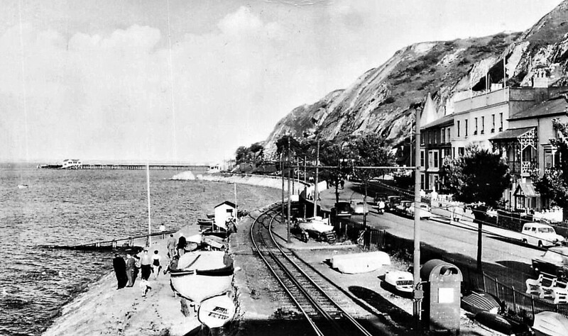 SWANSEA AND MUMBLES TRAMWAY - The Foreshore at Southend, Mumbles, after the 1929 electrification. The pier and the terminus of the railway is visible in the distance. <br /> The Swansea and Mumbles Railway was the world's first passenger railway service. Originally built under an Act of Parliament of 1804 to move limestone from the quarries of Mumbles to Swansea, it carried the world's first fare-paying railway passengers on March 25th, 1807. It later moved from horse power to steam locomotion in 1896, and finally converted to electric trams in 1929, before closing in January 1960, in favour of motor buses. The line was 5.5 miles long and converted to standard gauge in 1855. At the time of the railway's closure, it had been the world's longest serving railway.