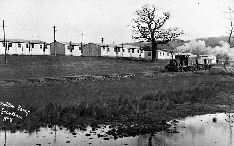 BELTON ARMY CAMP, Grantham - In 1914, Lord Brownlow of Belton House turned his park over to the Army who used it as a training base for 11th Northern Division. In 1915, it became the training base for the Machine Gun Corps. The camp was very large and had its own extensive standard gauge railway system. This branched off the GNR main line just south of Peascliffe Tunnel and then ran down Belton Lane, over the main Sleaford Road and into Belton Park, wherein there was quite a network of lines, with another running south right into Grantham and terminating near the old Garrison on New Beacon Road. The railway closed in 1922 and the park was handed back to his Lordship. This picture shows what appears to be a Manning Wardle 0-6-0ST running between the huts occupied by the 24th Manchesters and the small stream running from the lake. Note how the track is more or less just laid straight onto the ground with a minimal amount of ballast.
