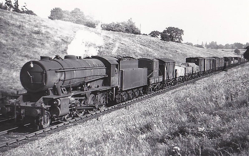 "77334 - WD Class 8F 2-8-0 - built 07/43 by North British Loco Co. as WD No.7334 - 01/45 to WD No.77334, 07/51 to BR No.90244 - 08/62 withdrawn from 33B Tilbury - seen here at Greenwood, 04/51,<br /> The War Department ""Austerity"" 2-8-0 is a type of heavy freight steam locomotive that was introduced in 1943 for war service. A total of 935 were built, making this one of the most-produced classes of British steam locomotive. The locomotive was a redesigned Stanier 8F, built for economy rather than longevity, 545 were built by the North British Loco Co. and the other 390 by the Vulcan Foundry. The whole class but for three served in Europe after D-Day and many returned to Britain postwar. 200 were sold to the LNER as Class O7 and a further 533 were sold to the BTC. These 733 became British Railways Class WD in 1948, numbered 90000 to 90732. In 1946, 12 were sold to the Kowloon - Canton Railway, 184 went to Holland as NS Class 4300 and 1 went to USATC. The WD retained 5 engines, scrapped 3 and the other two served on the Longmoor Military Railway."