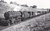 """77334 - WD Class 8F 2-8-0 - built 07/43 by North British Loco Co. as WD No.7334 - 01/45 to WD No.77334, 07/51 to BR No.90244 - 08/62 withdrawn from 33B Tilbury - seen here at Greenwood, 04/51,<br /> The War Department """"Austerity"""" 2-8-0 is a type of heavy freight steam locomotive that was introduced in 1943 for war service. A total of 935 were built, making this one of the most-produced classes of British steam locomotive. The locomotive was a redesigned Stanier 8F, built for economy rather than longevity, 545 were built by the North British Loco Co. and the other 390 by the Vulcan Foundry. The whole class but for three served in Europe after D-Day and many returned to Britain postwar. 200 were sold to the LNER as Class O7 and a further 533 were sold to the BTC. These 733 became British Railways Class WD in 1948, numbered 90000 to 90732. In 1946, 12 were sold to the Kowloon - Canton Railway, 184 went to Holland as NS Class 4300 and 1 went to USATC. The WD retained 5 engines, scrapped 3 and the other two served on the Longmoor Military Railway."""