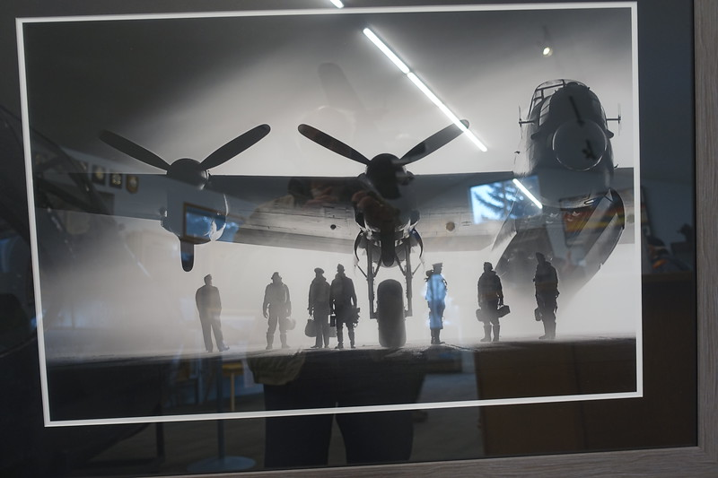 What attracted me to this framed photograph is the silhouetted airmen underneath their plane and gazing into the fog, and I knew quite well these reflections would interfere with my picture taking.